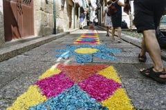 Guimaraes, Braga, Portogallo 14 agosto 2017: Il vicolo stretto del ciottolo con gli ornamenti molto variopinti si è formato dalle Fotografie Stock