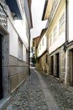 Guimaraes Braga, Portugal Augusti 14, 2017: Smal kullerstengränd med kullersten, inga personer som omkring går I backgrouen Fotografering för Bildbyråer