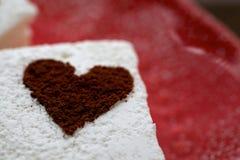 Guimauve avec le plan rapproché et l'espace rouges de plat de coeurs époussetés par cacao Photographie stock