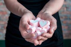 Guimauve en forme de coeur dans les mains de la fille Photos stock