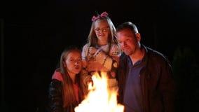 Guimauve heureuse de torréfaction de famille au-dessus de feu de camp banque de vidéos