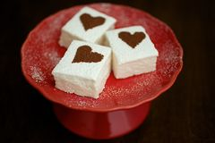 Guimauves avec les coeurs époussetés par cacao du plat rouge Images libres de droits