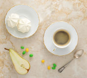Guimauves de petit déjeuner sur la soucoupe, une demi poire et une tasse de c Photographie stock libre de droits