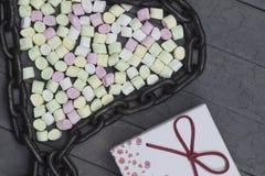 Guimauves disposées par forme de coeur avec la chaîne en métal concept d'amour sur le fond en bois Images stock