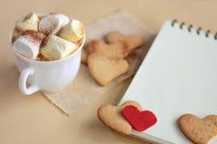 Guimauves et chocolat dans une tasse avec des biscuits Images stock