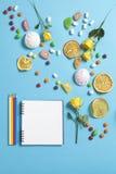Guimauves, sucrerie, dragées à la gelée de sucre, bonbons, oranges sèches de tasses et roses jaunes tombant sur un bloc-notes sur Photographie stock