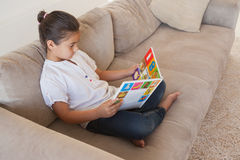 Guión relajado de la lectura de la muchacha en el sofá en la sala de estar Foto de archivo libre de regalías