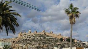 Guindaste contra o céu temperamental sobre o castelo de Almeria Imagens de Stock