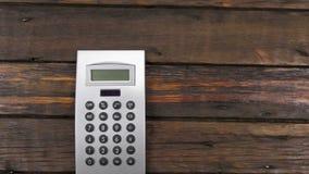Guindaste da câmera, movendo, calculadora que encontra-se em uma tabela de madeira bonita, velha com espaço da cópia video estoque