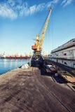 Guindaste da carga do porto sobre o fundo do céu azul Porto marítimo, guindaste para carregar no por do sol transporte fotos de stock royalty free