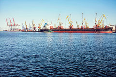Guindaste da carga do porto sobre o fundo do céu azul Porto marítimo, guindaste para carregar no por do sol transporte imagens de stock
