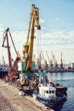 Guindaste da carga do porto sobre o fundo do céu azul Porto marítimo, guindaste para carregar no por do sol transporte imagem de stock royalty free