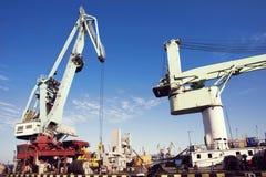 Guindaste da carga do porto sobre o fundo do céu azul Porto marítimo, guindaste para carregar no por do sol transporte imagem de stock