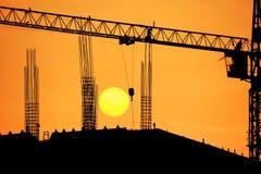 Guindaste da silhueta no local da construção civil Foto de Stock Royalty Free