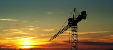 Guindaste de construção no por do sol Fotografia de Stock Royalty Free