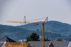 Guindaste de construção sobre os telhados da cidade fotos de stock