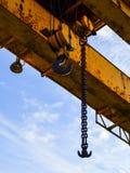 Guindaste de pórtico do gancho na corrente para levantar cargas pesadas no fundo de um feixe do metal e de um céu azul Canteiro d imagem de stock