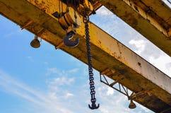 Guindaste de pórtico do gancho na corrente para levantar cargas pesadas no fundo de um feixe do metal e de um céu azul Canteiro d foto de stock royalty free