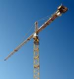 Guindaste de torre amarelo de encontro ao céu azul Imagem de Stock Royalty Free