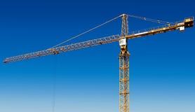 Guindaste de torre amarelo de encontro ao céu azul Fotos de Stock Royalty Free