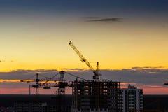 Guindaste de torre da construção, guindastes de construção industriais no fundo de surpresa do céu do por do sol imagem de stock royalty free