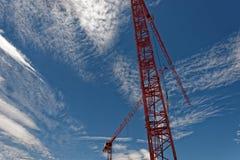 Guindaste de torre vermelho contra um céu azul Imagem de Stock