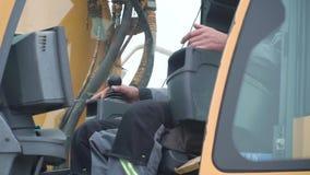 Guindaste do operador do coordenador na a??o grampo O homem na cabine controla o guindaste Senta uma parte superior na cabine e n filme