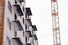 Guindaste e balcões altos da construção sob a construção no céu azul no dia de inverno nevado ensolarado Imagem de Stock