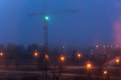Guindaste e iluminação de torre na noite, canteiro de obras Imagem de Stock Royalty Free