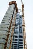 Guindaste unido ao lado da construção no canteiro de obras do centro Imagens de Stock Royalty Free