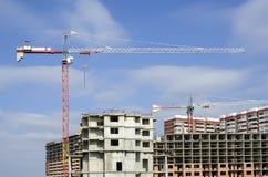 Guindastes de construção acima da área residencial Imagem de Stock