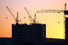 Guindastes de construção com as casas construídas no fundo do s Fotos de Stock