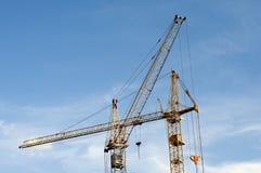 Guindastes de construção contra o céu fotos de stock