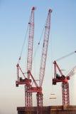 Guindastes de construção contra o céu azul Imagens de Stock