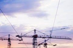 Guindastes de construção contra o céu no por do sol imagens de stock royalty free