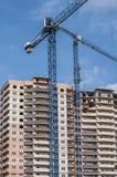 Guindastes de construção contra um fundo do prédio imagens de stock