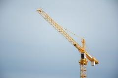 Guindastes de construção industriais em um fundo do céu azul Fotos de Stock