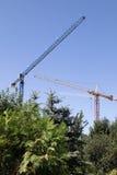 Guindastes de construção mostrados em silhueta de encontro ao céu azul Foto de Stock