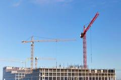 Guindastes de construção, construção no fundo do céu azul imagem de stock