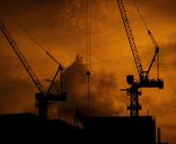 Guindastes de construção no prédio com o céu e as nuvens alaranjados dramáticos no tempo do por do sol na noite Canteiro de obras foto de stock royalty free