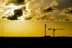 Guindastes de construção sob um céu drmatic fotos de stock