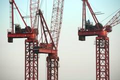 Guindastes de construção vermelhos contra o céu azul Fotografia de Stock Royalty Free