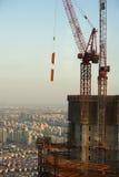 Guindastes de construção vermelhos contra o céu azul Imagens de Stock