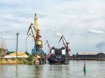 Guindastes de doca em um porto marítimo pequeno Fotografia de Stock