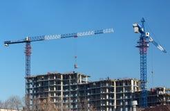 Guindastes e local da construção civil contra o céu azul Fotografia de Stock
