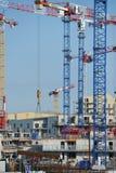 Guindastes e local de construção contra um céu azul Fotografia de Stock