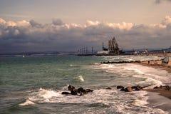 Guindastes e mar da carga sob o céu tormentoso Fotografia de Stock Royalty Free