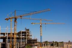 Guindastes e prédio de torre da construção sob a construção contra o céu azul Imagem de Stock Royalty Free