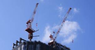Guindastes móveis na construção inferior atrás do céu azul no Tóquio video estoque