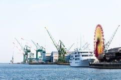 Guindastes no porto com roda de ferris Imagem de Stock Royalty Free